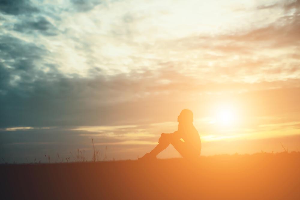 座っている女性と夕日